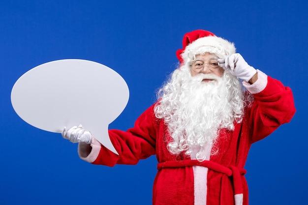 Widok z przodu święty mikołaj trzymający duży biały znak na niebieskim kolorze śniegu wakacje bożego narodzenia