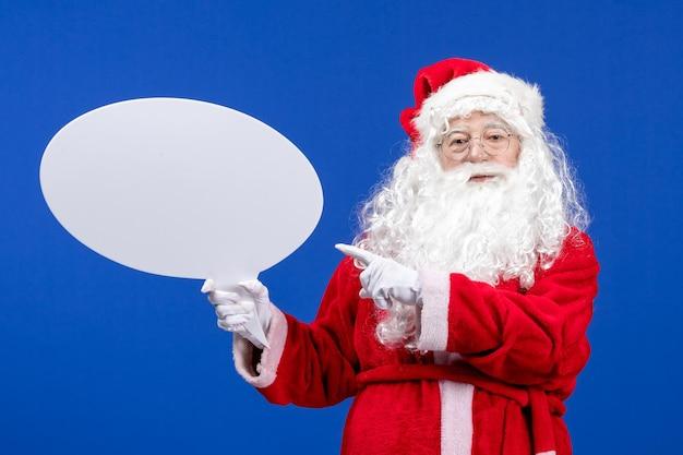 Widok z przodu święty mikołaj trzymający duży biały znak na niebieskim świątecznym kolorze śniegu
