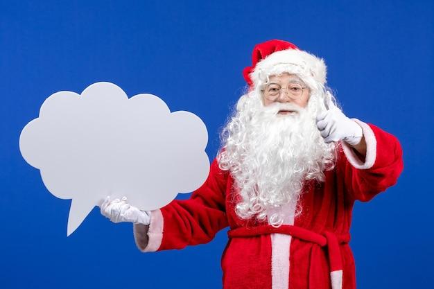 Widok z przodu święty mikołaj trzymający duży biały znak w kształcie chmury na niebieskim kolorze śniegu wakacje bożego narodzenia