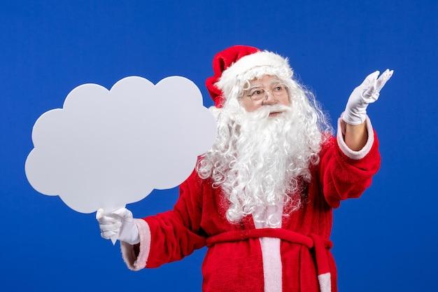 Widok z przodu święty mikołaj trzymający duży znak w kształcie chmury na niebieskim kolorze śniegu boże narodzenie