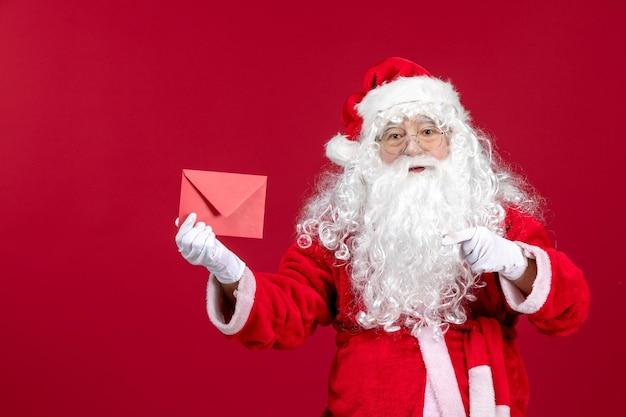 Widok z przodu święty mikołaj trzymający kopertę z listem życzeń od dziecka na czerwonych emocjach nowego roku
