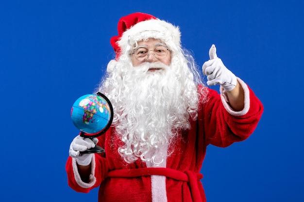 Widok z przodu święty mikołaj trzymający małą kulę ziemską na niebieskim kolorze nowego roku święta bożego narodzenia