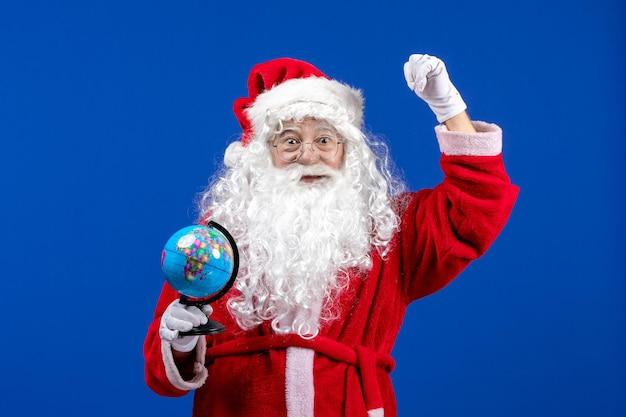 Widok z przodu święty mikołaj trzymający małą kulę ziemską na niebieskim kolorze świątecznych świąt