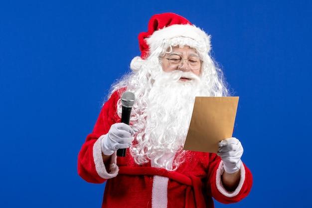 Widok z przodu święty mikołaj trzymający mikrofon i czytający list na niebieskim kolorze nowego roku świąteczny śnieg