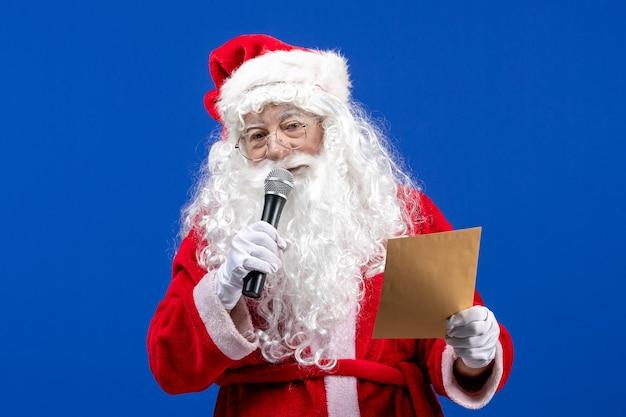 Widok z przodu święty mikołaj trzymający mikrofon i czytający list na niebieskim kolorze nowego roku święta bożego narodzenia śnieg