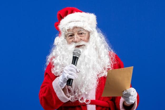 Widok z przodu święty mikołaj trzymający mikrofon i czytający list na niebieskim nowym roku śniegu w kolorze świątecznym