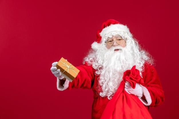 Widok z przodu święty mikołaj trzymający prezent z torby pełnej prezentów dla dzieci na czerwony emocja nowy rok