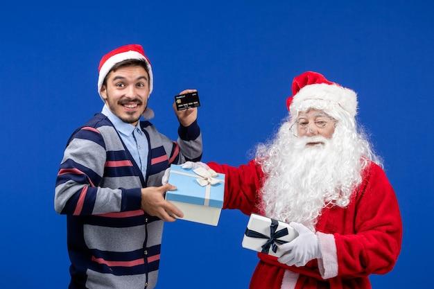 Widok z przodu święty mikołaj trzymający prezenty i młody mężczyzna trzymający kartę bankową na niebieskich świątecznych świętach