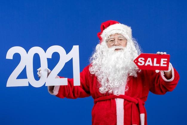 Widok z przodu święty mikołaj trzymający sprzedaż i pisma na niebieskim kolorze śniegu wakacje nowy rok boże narodzenie