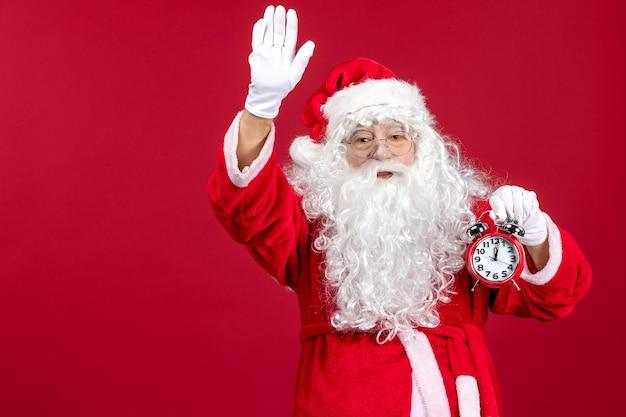 Widok z przodu święty mikołaj trzymający zegar na czerwonych świątecznych emocjach noworocznych