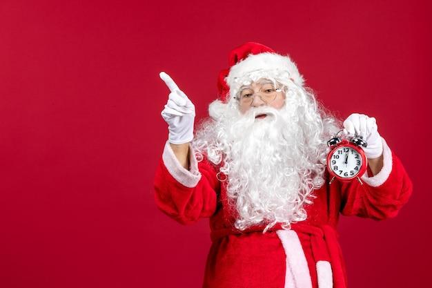 Widok z przodu święty mikołaj trzymający zegar na czerwonych świątecznych emocjach świętach nowego roku