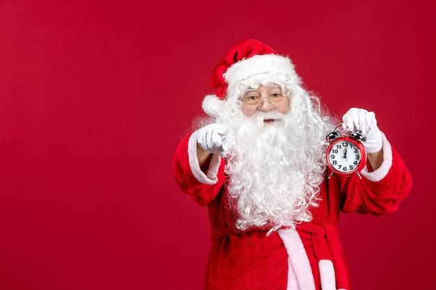 Widok z przodu święty mikołaj trzymający zegar na czerwonym świątecznym emocjach świątecznych nowego roku
