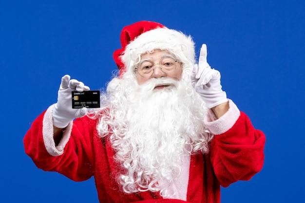 Widok z przodu święty mikołaj w czerwonych ubraniach z białym misiem trzymającym czarną kartę bankową w kolorze niebieskim