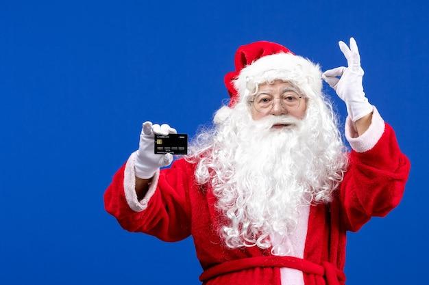 Widok z przodu święty mikołaj w czerwonym garniturze trzymający czarną kartę bankową na niebieskim biurku świąteczny prezent świąteczny