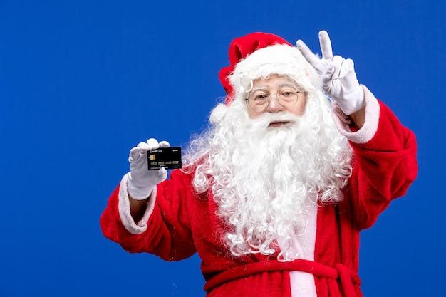 Widok z przodu święty mikołaj w czerwonym garniturze trzymający czarną kartę bankową na niebieskim obecnym świątecznym kolorze świątecznym