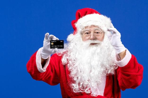 Widok z przodu święty mikołaj w czerwonym garniturze trzymający czarną kartę bankową na niebieskim świątecznym prezentie