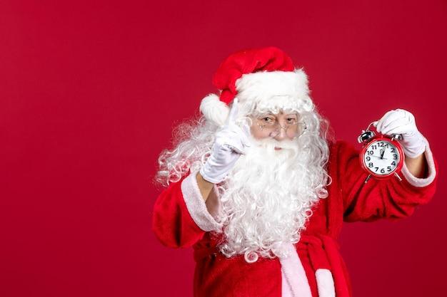Widok z przodu święty mikołaj w czerwonym garniturze trzymający zegar na czerwonym świątecznym czasie emocji świątecznych