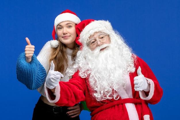 Widok z przodu święty mikołaj wraz z młodą kobietą na niebieskich ludzkich świętach w kolorze świąt noworocznych