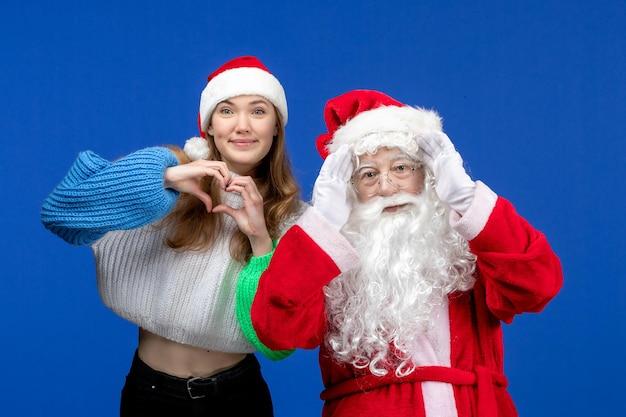 Widok z przodu święty mikołaj wraz z młodą kobietą na niebieskich świętach ludzki kolor bożego narodzenia nowy rok