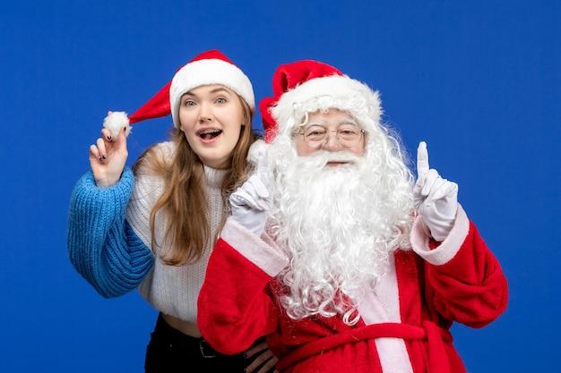 Widok z przodu święty mikołaj wraz z młodą kobietą na niebieskim ludzkim bożego narodzenia w kolorze świąt noworocznych