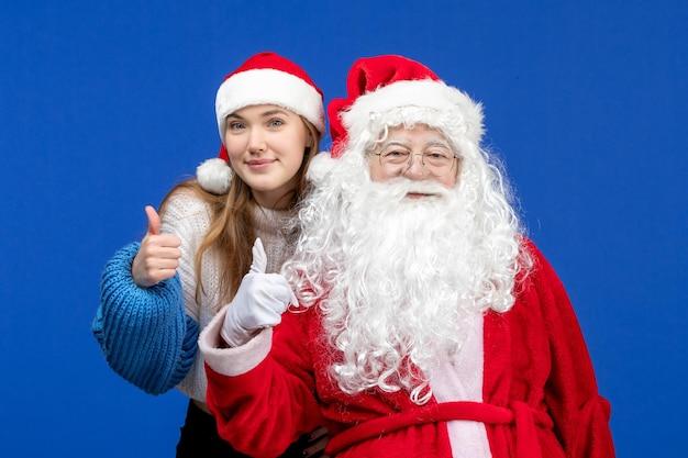 Widok z przodu święty mikołaj wraz z młodą kobietą na niebieskim ludzkim kolorze bożego narodzenia w nowym roku