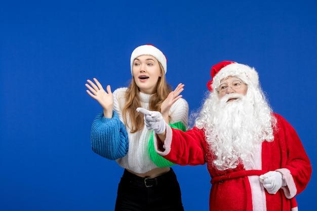 Widok z przodu święty mikołaj wraz z młodą kobietą stojącą na niebieskich świątecznych emocjach świątecznych nowego roku