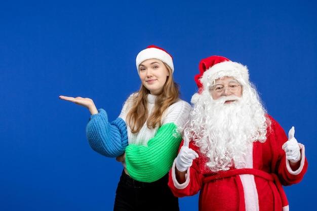 Widok z przodu święty mikołaj wraz z młodą kobietą stojącą na niebieskich świątecznych świątecznych kolorach emocji