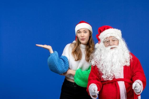 Widok z przodu święty mikołaj wraz z młodą kobietą stojącą na niebieskiej podłodze nowy rok świąteczny kolor