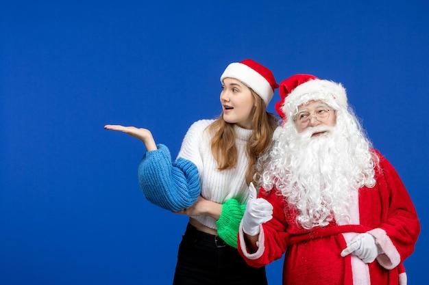 Widok z przodu święty mikołaj wraz z młodą kobietą stojącą na niebieskim biurku nowy rok świąteczny kolor