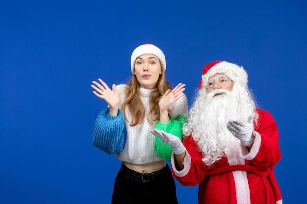 Widok z przodu święty mikołaj wraz z młodą kobietą stojącą na niebieskim świątecznym nowym roku