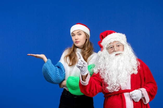 Widok z przodu święty mikołaj wraz z młodą kobietą stojącą na niebieskim świątecznym świątecznym kolorze emocji