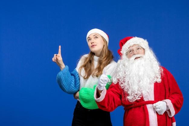 Widok z przodu święty mikołaj wraz z młodą kobietą stojącą na niebieskim świątecznym świątecznym kolorze świątecznych emocji