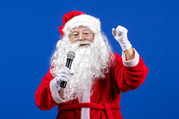Widok z przodu święty mikołaj z czerwonym garniturem i białą brodą trzymającą mikrofon na niebieskim kolorze bożego narodzenia