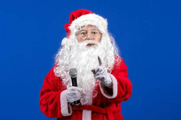 Widok z przodu święty mikołaj z czerwonym garniturem i białą brodą trzymającą mikrofon na niebieskim kolorze noworocznych emocji świątecznych