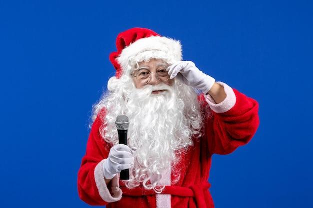 Widok z przodu święty mikołaj z czerwonym garniturem i białą brodą trzymającą mikrofon na niebieskim kolorze śniegu wakacje boże narodzenie nowy rok