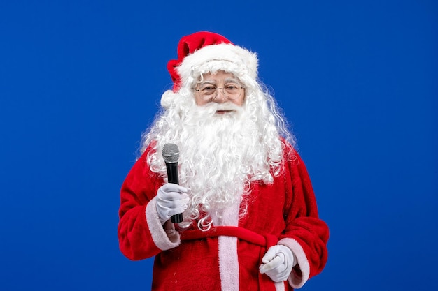 Widok z przodu święty mikołaj z czerwonym garniturem i białą brodą trzymającą mikrofon na niebieskim kolorze świątecznym nowego roku