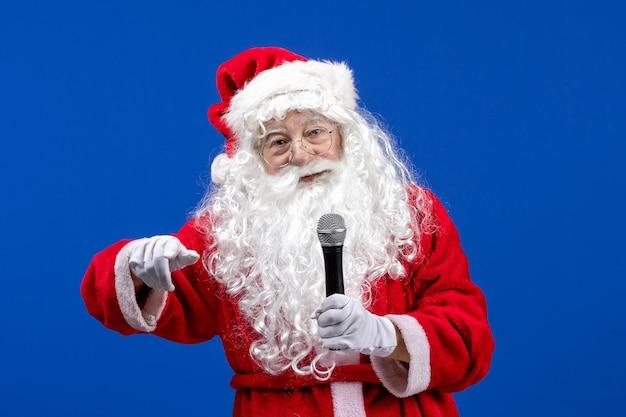 Widok z przodu święty mikołaj z czerwonym garniturem i białą brodą trzymającą mikrofon na niebieskim śniegu świątecznym kolorze