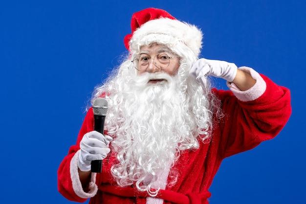 Widok z przodu święty mikołaj z czerwonym garniturem i białą brodą trzymającą mikrofon na niebieskim świątecznym kolorze nowego roku