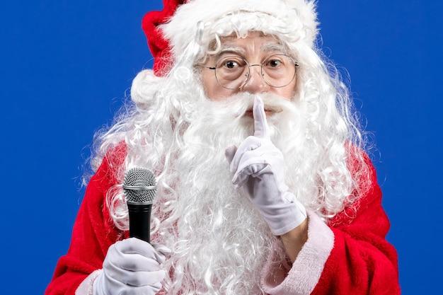 Widok z przodu święty mikołaj z czerwonym garniturem i białą brodą trzymającą mikrofon na niebieskim świątecznym kolorze