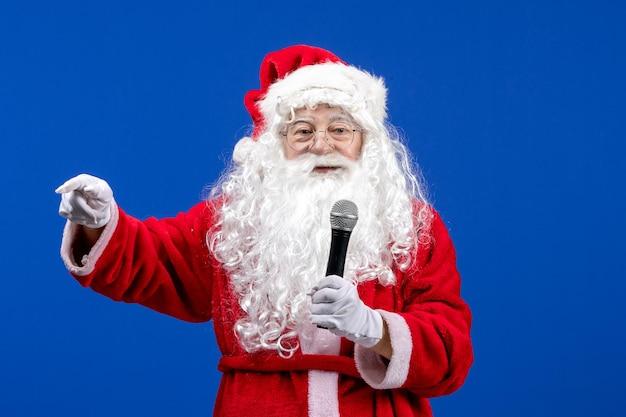 Widok z przodu święty mikołaj z czerwonym garniturem i białą brodą trzymającą mikrofon na niebieskim świątecznym świątecznym kolorze