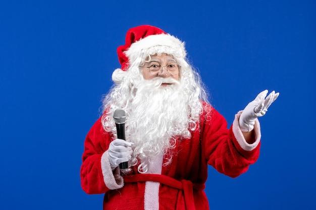 Widok z przodu święty mikołaj z czerwonym garniturem i białą brodą trzymającą mikrofon na niebieskim święcie noworocznym