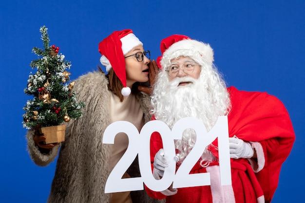 Widok z przodu święty mikołaj z kobietą trzymającą pisanie i małą choinką na niebieskim kolorze nowego roku
