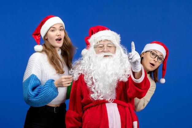 Widok z przodu święty mikołaj z kobietami na niebieskim zimnym świątecznym emocjach śnieg nowy rok