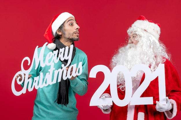 Widok z przodu święty mikołaj z męskim trzymaniem i wesołymi napisami bożonarodzeniowymi na czerwonym prezencie świątecznym
