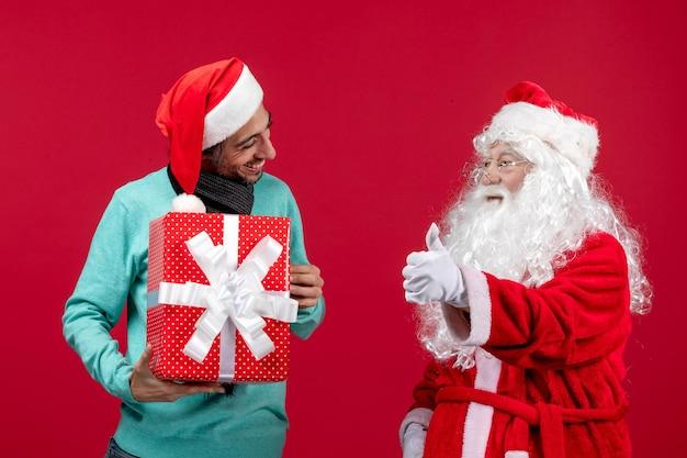 Widok z przodu święty mikołaj z mężczyzną trzymający prezent świąteczny na czerwonym emocji czerwony prezent świąteczny nowy rok