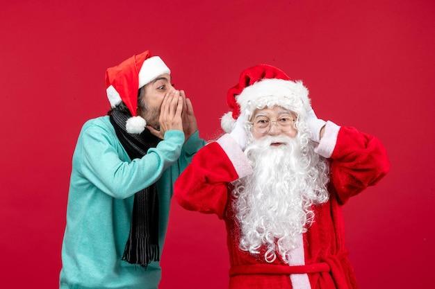 Widok z przodu święty mikołaj z mężczyzną w interakcji na czerwonym teraźniejszości świątecznych emocji wakacje nowy rok