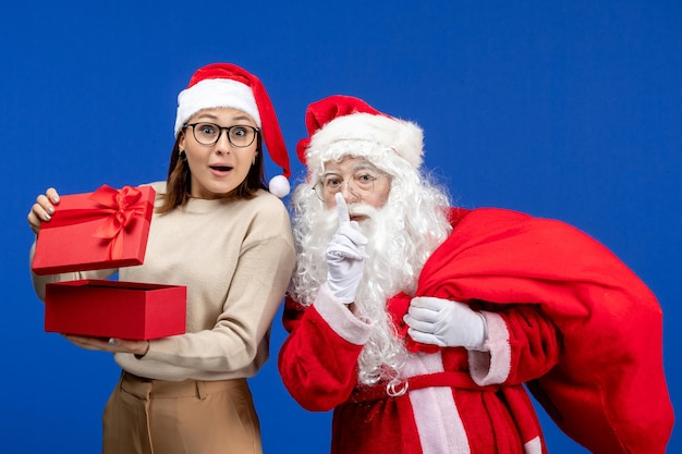 Widok z przodu święty mikołaj z młodą kobietą, która otwiera się na niebieskim biurku świąteczna emocja śnieżna
