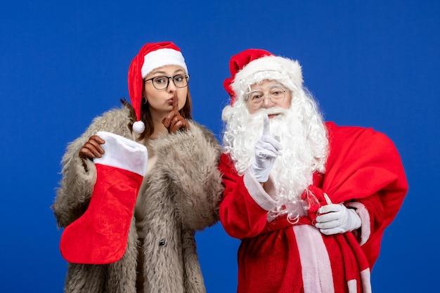 Widok z przodu święty mikołaj z młodą kobietą trzymającą torbę i czerwoną skarpetę na niebieskim świątecznym