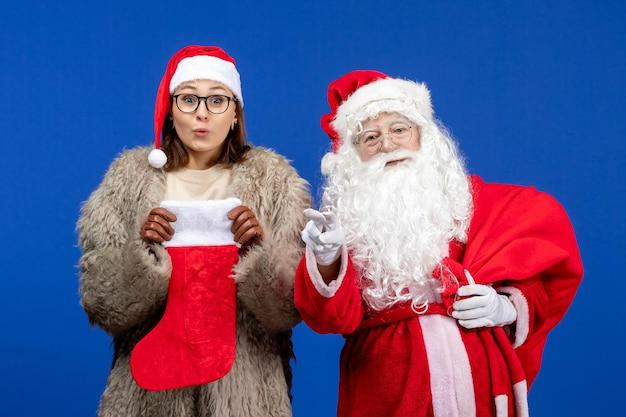 Widok z przodu święty mikołaj z młodą kobietą trzymającą torbę i czerwoną skarpetę w niebieskim kolorze świątecznym