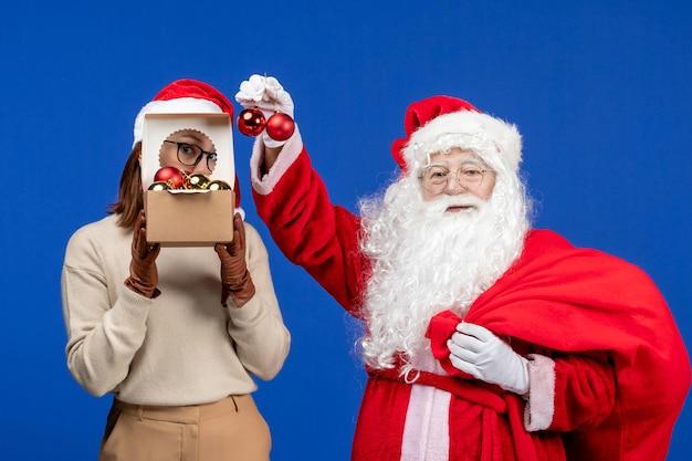 Widok z przodu święty mikołaj z młodą kobietą trzymającą torbę z prezentami i zabawkami na niebieskich świątecznych świętach